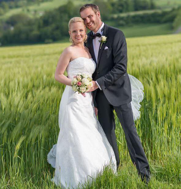 Das glückliche Brautpaar einer Hochzeit im Romantik Hotel Platte auf einem Feld.