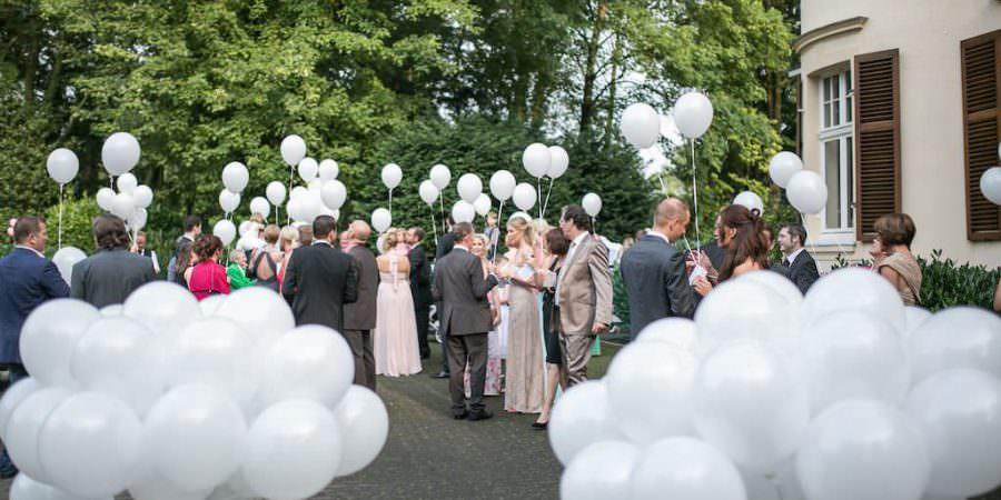 Gäste einer Hochzeit in der Bayer Villa empfangen das Brautpaar mit weißen Luftballons.