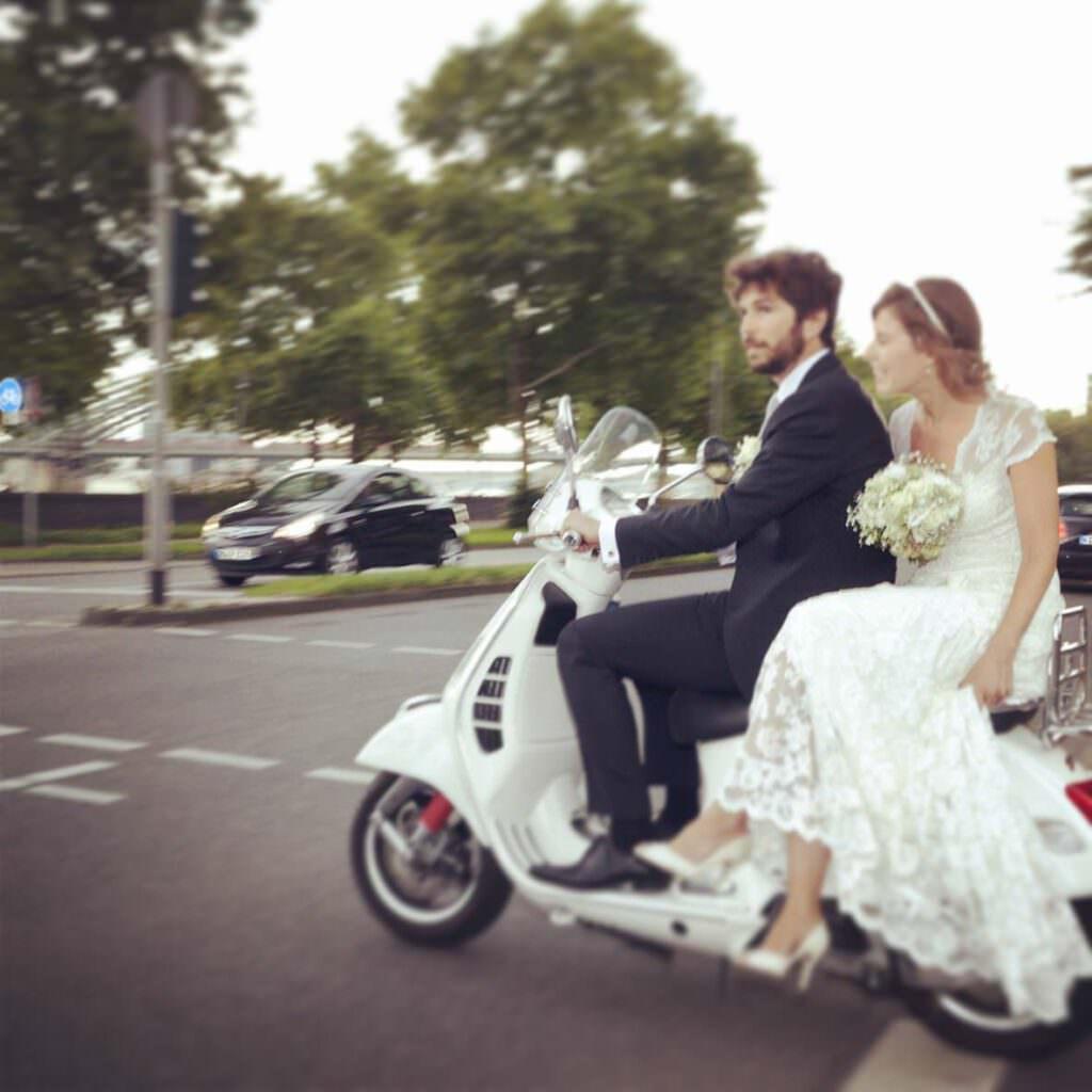 Das Brautpaar einer deutsch-französischen Hochzeit in den Rheinterrassen kommt auf einer Vespa an.
