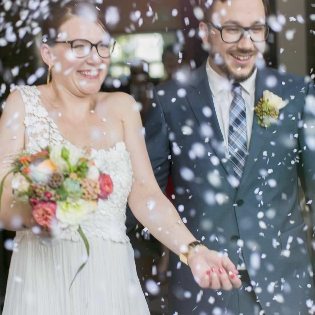 Originelles Hochzeitsfoto vom Brautpaar, das mit viel Streudeko beworfen wird.