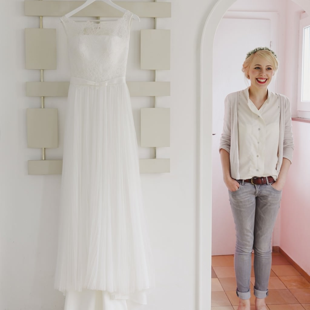 Hochzeitsfotoidee beim Getting Ready: Die Braut steht neben ihrem Brautkeid.