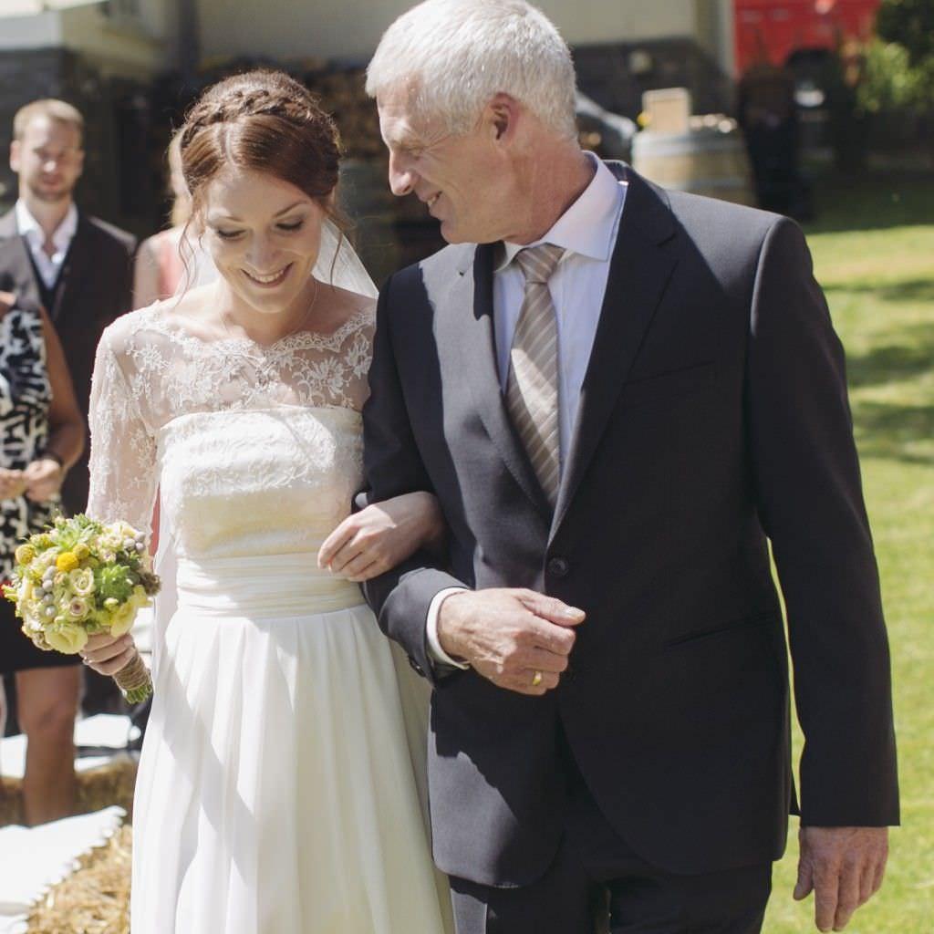 Die Braut läuft am Arm ihres Vaters zur Trauung.