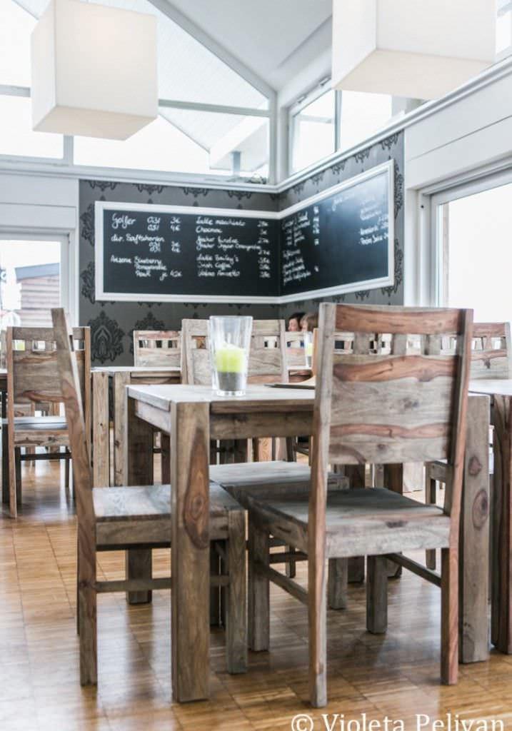 Menütafel und rustikale Holztische und Stühle in der Hochzeitslocation Trüffelschwein bei Düsseldorf.