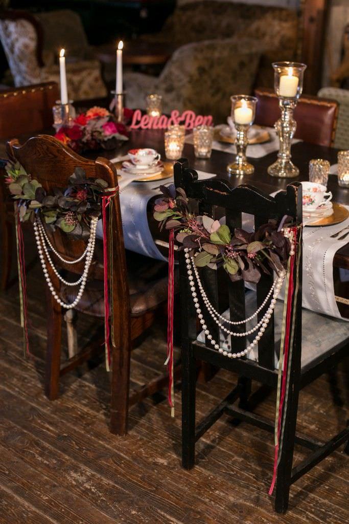Vintage Hochzeitsstühle, dekoriert mit Blumenkränzen und Perlenketten
