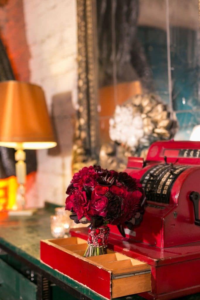 Vintage Dekoaccessoires und rote Blumen in der Hochzeitslocation Gare du Neuss