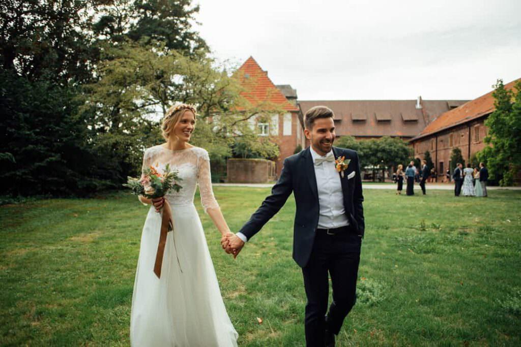 Das Hochzeitspaar Hand in Hand auf einer Wiese von Gutshof Ladenburg