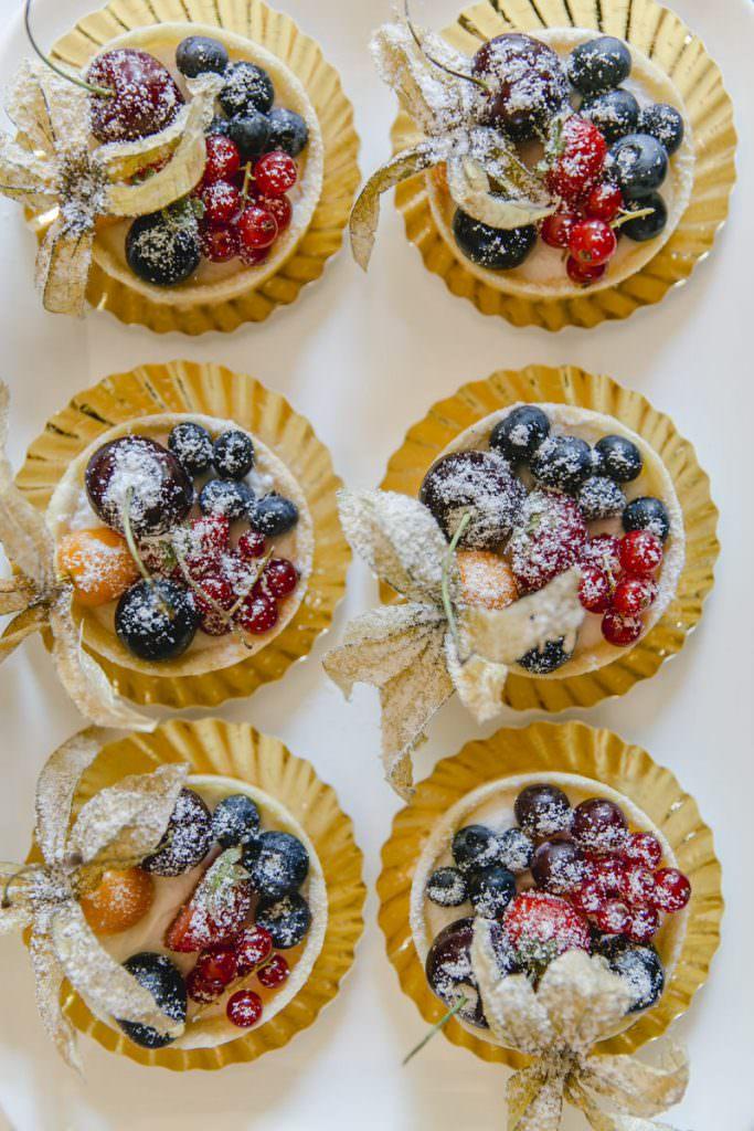 mit Puderzucker bestäubte Obsttörtchen auf dem Kuchenbuffet einer Hochzeit