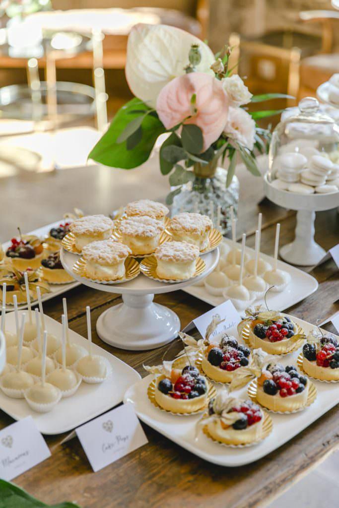 Törtchen mit Obst und Creme, weiße Cake Pops und Macarons auf dem Sweet Table einer Hochzeit