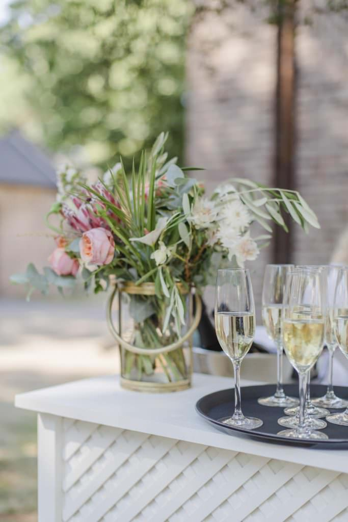 Hochzeitsdeko mit rosafarbenen Blumen, Eukalyptus, Olivenzweigen und Palmenblättern