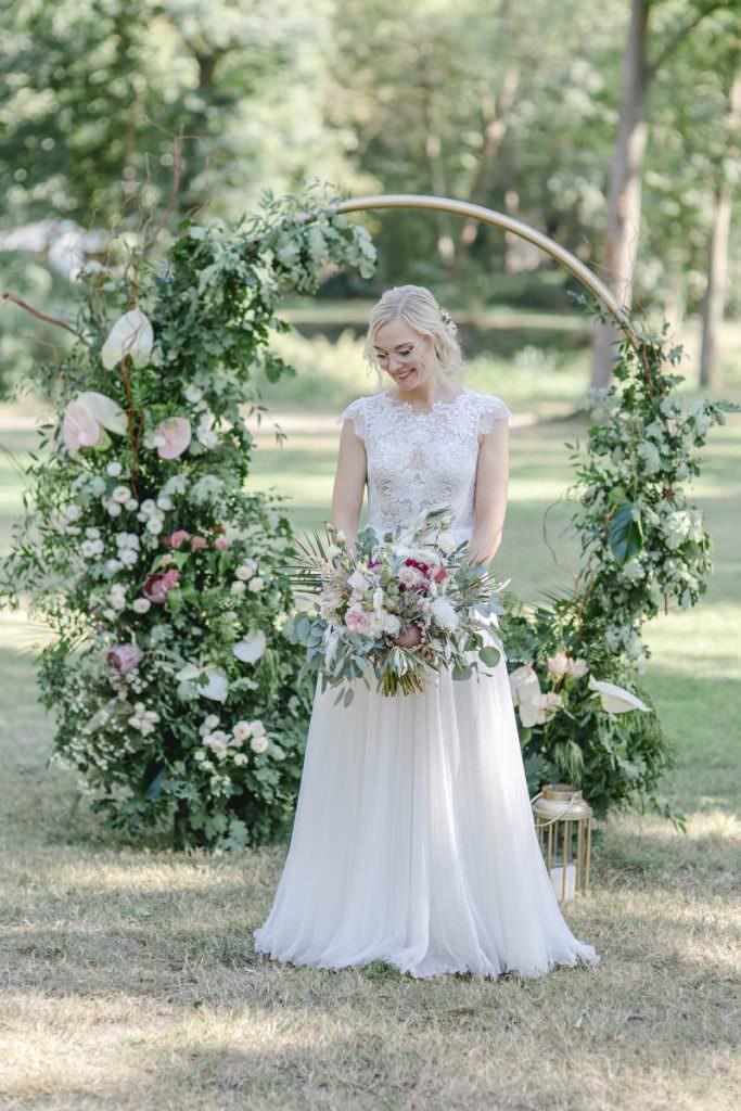 Brautportrait mit Brautstrauß vor einem runden Greenery Traubogen mit hellen Blumen