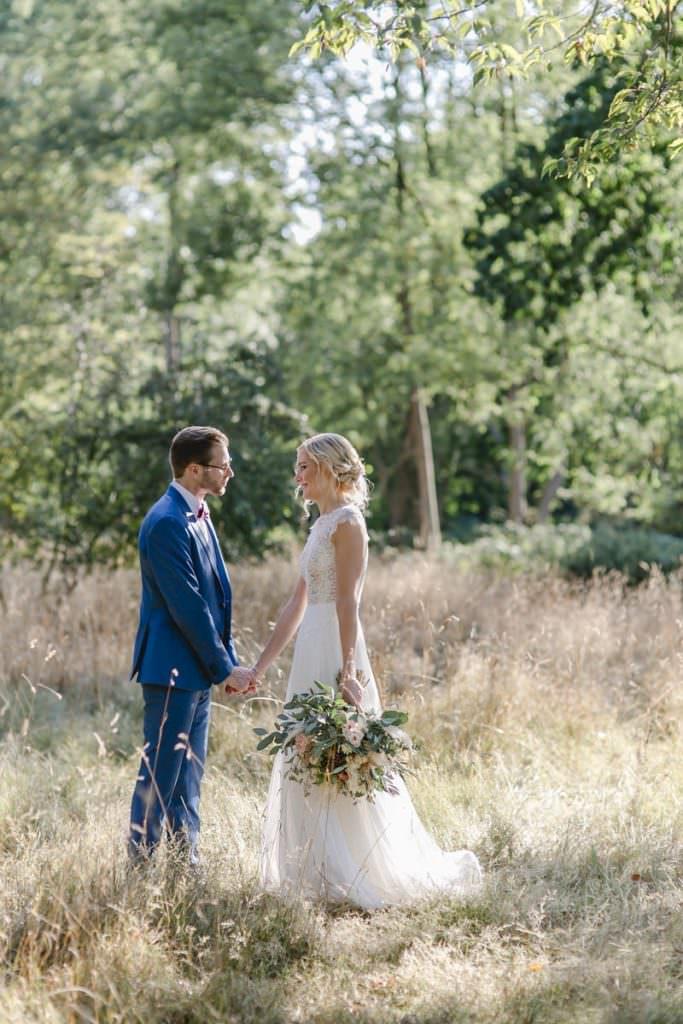 Corona-Hochzeit Rittergut Orr: Romantisches Paarfoto zwischen hohen Gräsern.