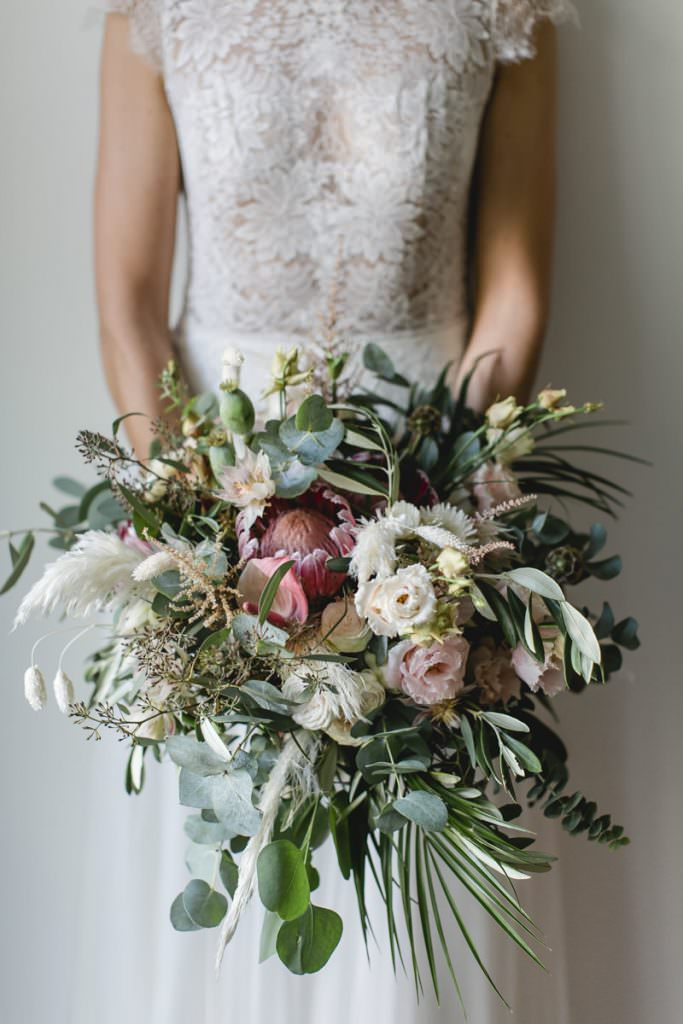 moderner Boho Brautstrauß mit pinkfarbener Protea, Pampasgras, Eukalyptus und Blumen in Rosa und Weiß