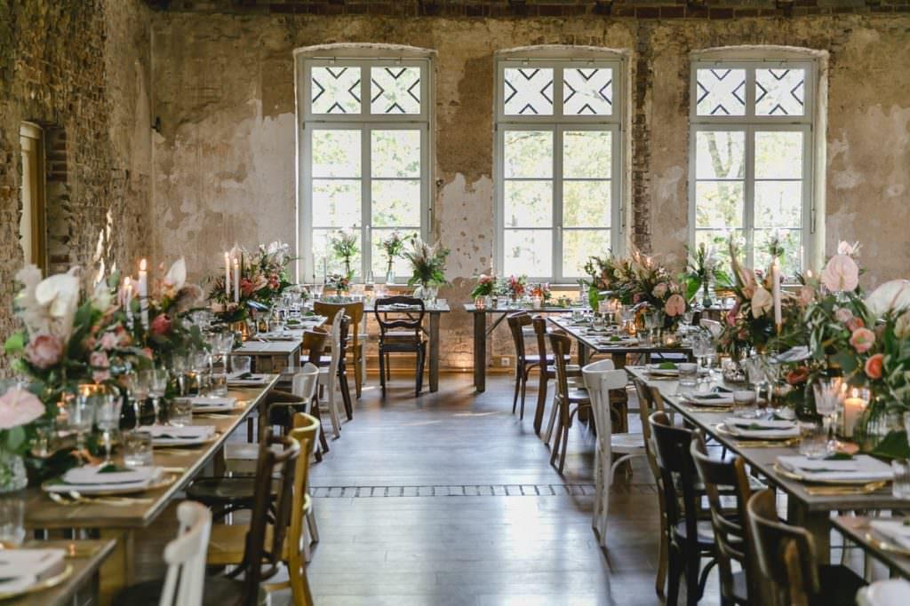 Corona-Hochzeit Rittergut Orr Festsaal mit rustikalen Holztischen und moderner Blumendeko.
