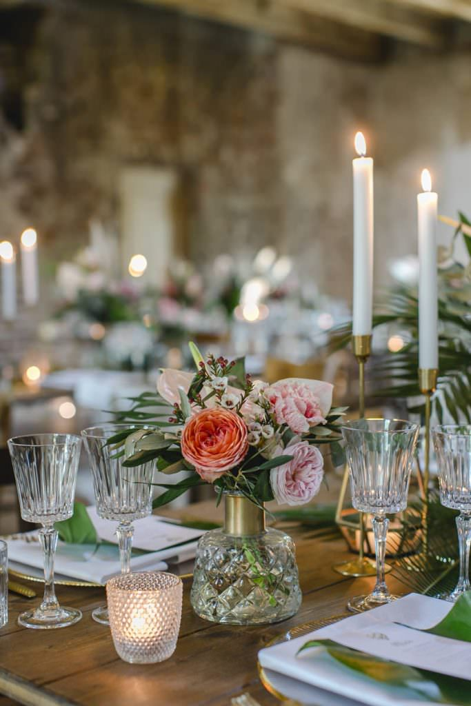 Hochzeitstischdeko mit goldenen Kerzenleuchtern, Kristallgläsern und Blumen in Rosa und Weiß.