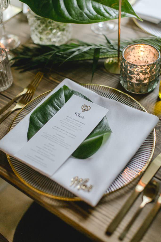 Weiße Hochzeitsmenükarte mit geometrischem, goldenen Herzen, die auf einem grünen Blatt liegt.