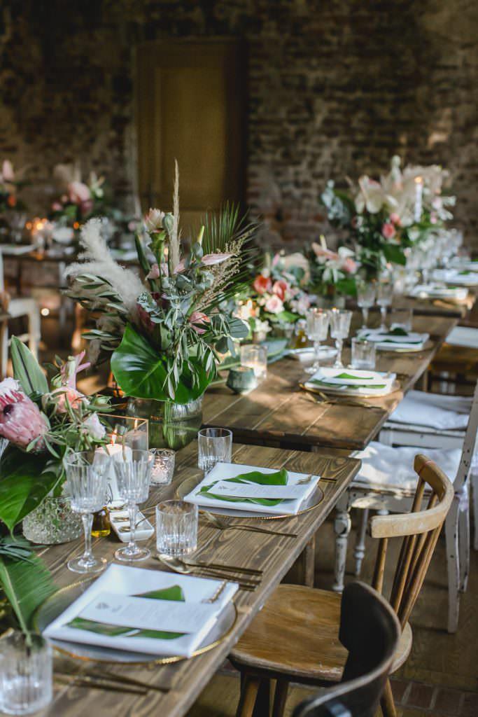 Hochzeitstischdeko mit Eukalyptus, Pampasgras, Protea, Olivenzweigen und Palmenblättern.