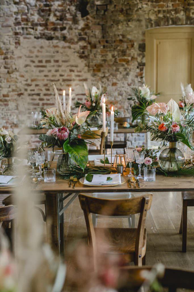 Hochzeitstischdeko mit viel Greenery, Palmenblättern und Protea, Flamingoblumen und Rosen in Rosa.