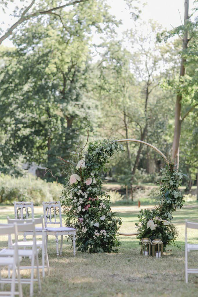Corona-Hochzeit Rittergut Orr: Freie Trauung auf der Wiese mit Greenery Traubogen und weißen Stühlen