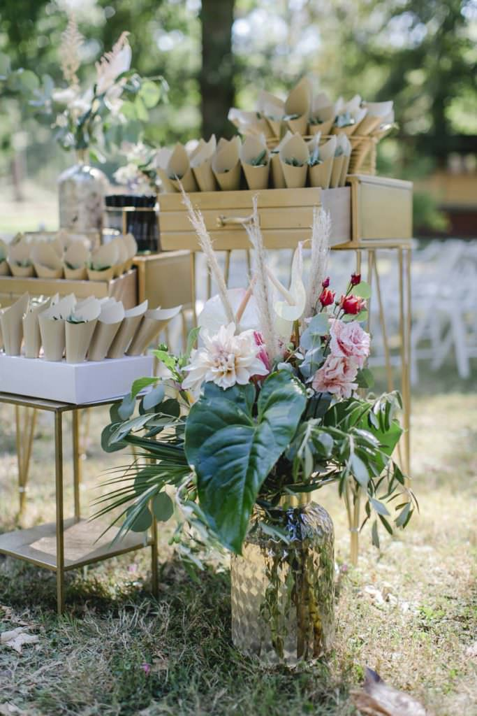 Üppige Hochzeitsdeko mit verschiedenen Blumen in Rosa, Pampasgras, Eukalyptus und Palmenblättern