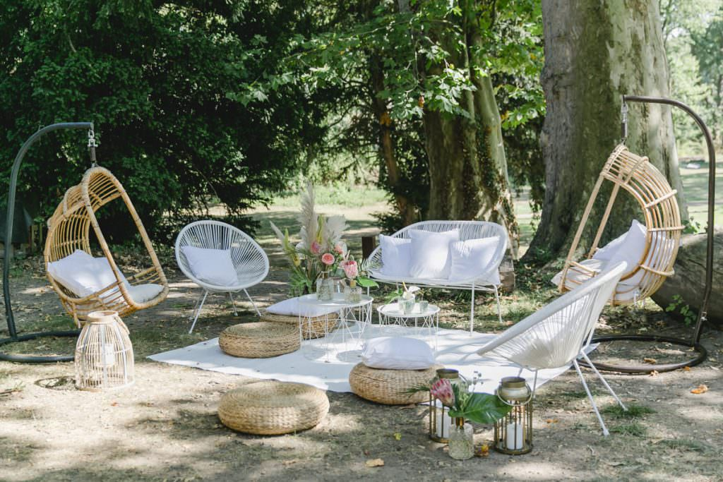 Lounge Ecke bei einer Outdoor Hochzeit mit weißen Acapulco Chairs, Rattan-Hängesesseln und Rattan Bodenhockern