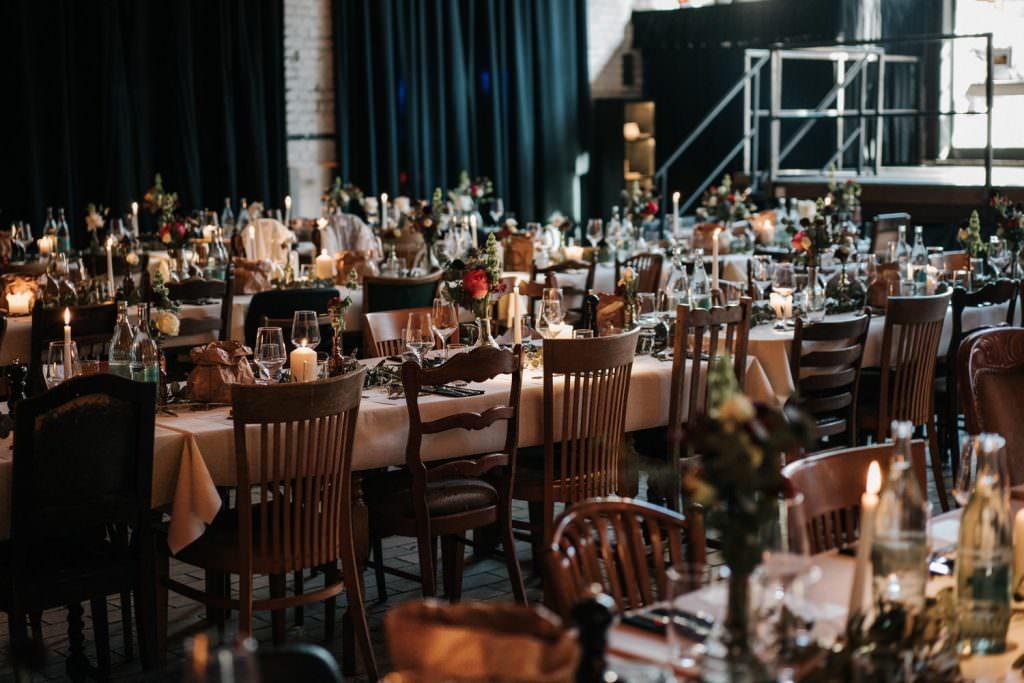 Seifenfabrik Düsseldorf Festsaal mit rustikalen Holzstühlen und gedeckten Hochzeitstischen