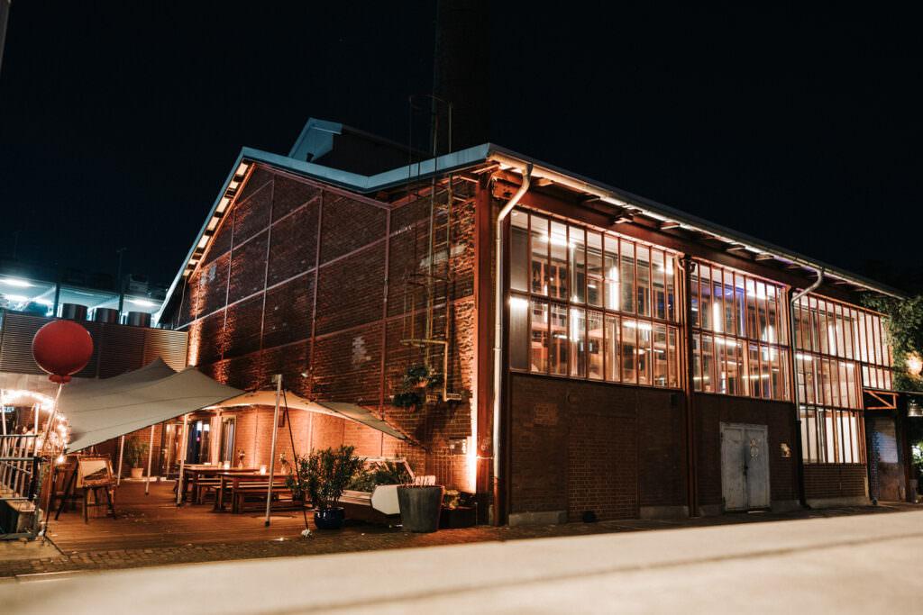 Außenansicht der beleuchteten Industrie-Stil Hochzeitslocation Seifenfabrik Dr. Thompson's in Düsseldorf