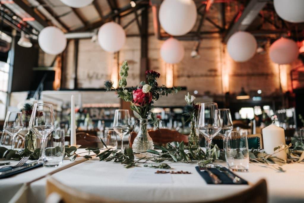 Hochzeitsdeko in der Seifenfabrik Düsseldorf mit Eukalyptus auf den Tischen und weißen Luftballons unter der Decke