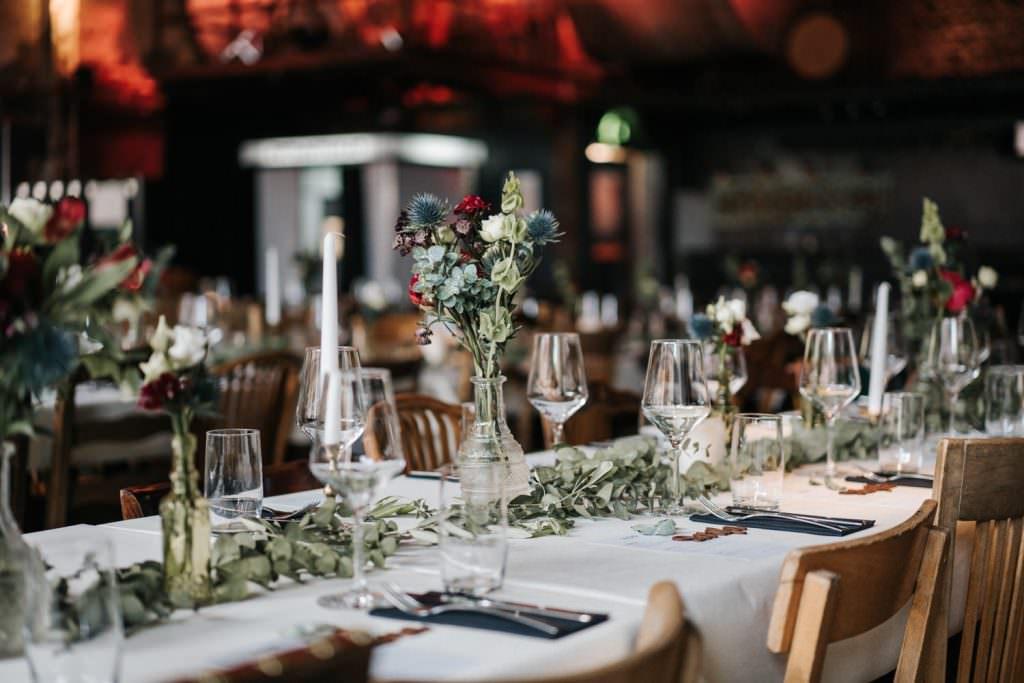 Hochzeitsdeko mit Eukalyptus als Tischgirlande und Blumenvasen mit Disteln, Rosen und Eukalyptus