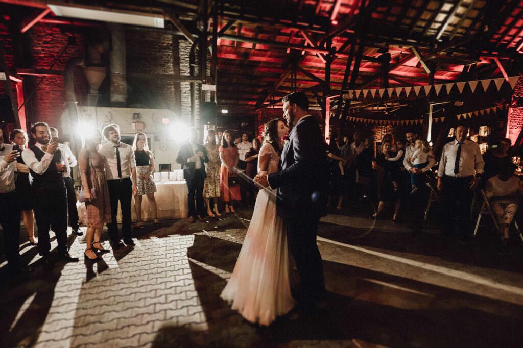 Hochzeitspaar tanzt alleine auf Tanzfläche unter stimmungsvollem Licht.
