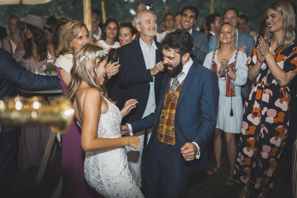 Ein Hochzeitspaar tanzt ausgelassen auf ihrer Hochzeitsparty.