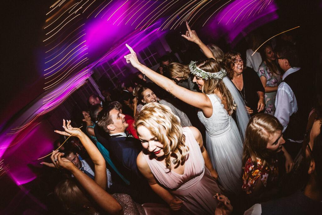 Tanzende Hochzeitsgäste unter pinkfarbenem Diskolicht recken die Hände in die Höhe.